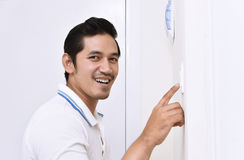 Handsome asian man turning off the light with wall switch Stock Image