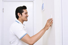 Handsome asian man turning off the light with wall switch. In the home royalty free stock photography