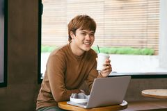 Handsome asian man using laptop sitting on wooden table in coffee shop with a cup of coffee stock image