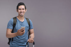 Handsome asian man using mobile phone while holding suitcase stock photo