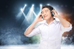 Handsome asian man in white shirt with headphones enjoy the music. Over concert spot lighting and smoke with defocused colorful lights background royalty free stock image