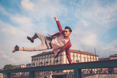 Handsome Asian model jumping in the city streets Stock Photos