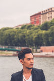 Handsome Asian model posing by an artificial basin Royalty Free Stock Photos