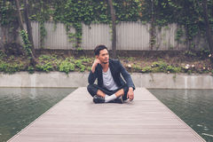 Handsome Asian model posing by an artificial basin Stock Photography