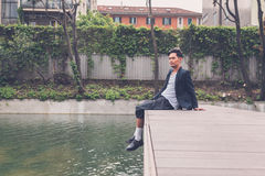 Handsome Asian model posing by an artificial basin Stock Image