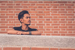 Handsome Asian model posing with a brick wall in background Stock Photo