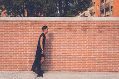Handsome Asian model posing with a brick wall in background Stock Photography