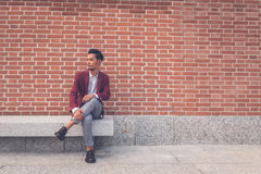 Handsome Asian model sitting in the city streets Royalty Free Stock Images
