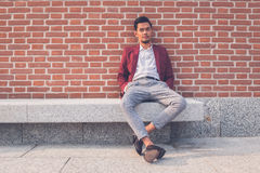 Handsome Asian model sitting in the city streets Stock Photo