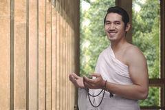 Handsome asian muslim male with ihram holding prayer beads Royalty Free Stock Images