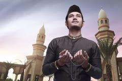 Handsome asian muslim man holding prayer beads and praying Stock Photos