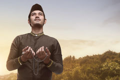 Handsome asian muslim man holding prayer beads and praying Royalty Free Stock Photography