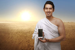 Handsome asian muslim man with ihram clothes showing phone Royalty Free Stock Photography