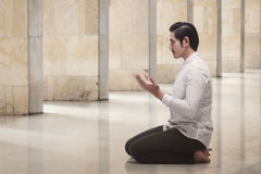 Handsome asian muslim man kneeling while praying Stock Photos