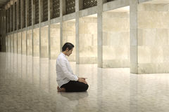 Handsome asian muslim man kneeling and praying to god Stock Image