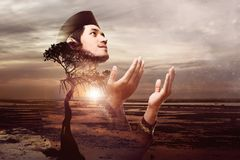 Handsome asian muslim man pray to god. At sunset on the beach. Double Exposure effect Royalty Free Stock Photography
