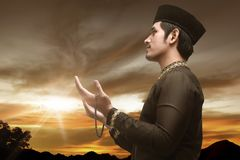 Handsome asian muslim man with prayer beads. At sunset background Royalty Free Stock Image