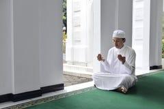 Handsome asian muslim man raising hand and praying Royalty Free Stock Image