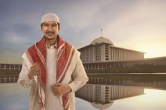 Handsome asian muslim man with traditional dress holding prayer Royalty Free Stock Photography