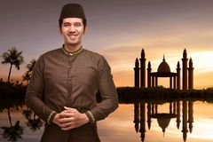 Handsome asian muslim man with traditional dress standing in fro. Nt of the mosque at sunset stock photos