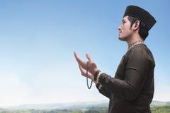 Handsome asian muslim man wearing cap praying Stock Image