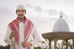 Handsome asian muslim man with white cap holding prayer beads Royalty Free Stock Image