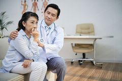 Calming down Senior Patient. Handsome Asian physician sitting on sofa of modern office and calming down sad senior women after announcement of diagnosis stock photography
