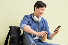 Free Handsome Asian Student Boy Sitting Using Smart Phone Royalty Free Stock Photos - 216677478