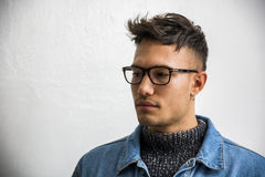 Handsome asian-white young man wearing grey sweater. Handsome white asian young man wearing blue denim jacket, standing on light background against wall in Stock Images