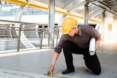 Handsome asian worker or engineer man is measuring the floor by royalty free stock photography
