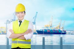 Handsome asian worker with yellow hard hat standing on the office. With industrial harbor and blue sky background royalty free stock photo
