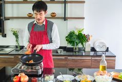Handsome, Asian young man Smiling happiness.  Frying sausages in a pan for  food stock photo