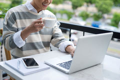Handsome asian young man working on laptop and smiling while enj Stock Photos