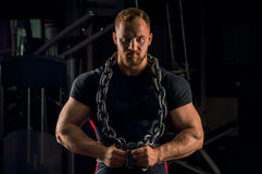 Handsome athlete with a chain around his neck stands in the gym stock images