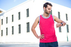Handsome athlete checking time with hands on hips Stock Photography