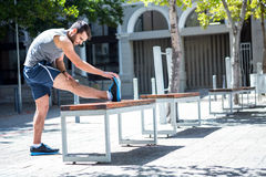 Handsome athlete doing leg stretching on a bench Royalty Free Stock Photos