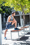 Handsome athlete doing leg stretching on a bench Stock Photos