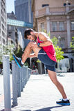 Handsome athlete doing leg stretching on a stake Stock Photos