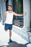 Handsome athlete doing leg stretching Royalty Free Stock Image