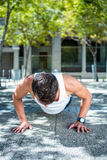 Handsome athlete doing push ups. In the city Stock Image