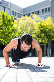 Handsome athlete doing push-ups on the floor. Determined athlete doing push-ups on the floor on a sunny day Royalty Free Stock Photos