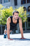 Handsome athlete doing push-ups on the floor. Determined athlete doing push-ups on the floor on a sunny day Stock Photos