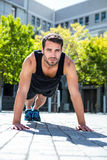 Handsome athlete doing push-ups on the floor. On a sunny day Stock Images