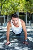 Handsome athlete doing push ups. Portrait of handsome athlete doing push ups in the city Royalty Free Stock Photo