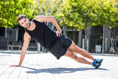 Handsome athlete doing a side plank. Portrait of an handsome athlete doing side plank on a sunny day royalty free stock image
