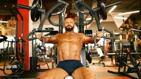 Handsome athlete is exercising in gym centre. Bodybuilder man hard training muscles at training machine. stock video