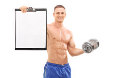 Handsome athlete holding barbell and a clipboard Royalty Free Stock Photography