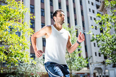Handsome athlete jogging in front of buildings Royalty Free Stock Photography