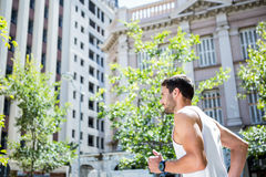 Handsome athlete jogging in front of buildings Stock Image