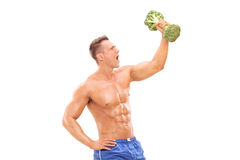 Handsome athlete lifting a broccoli dumbbell Royalty Free Stock Image